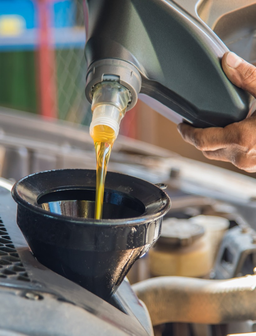 Mechanic topping up engine oil fluids - Car Servicing, Diagnostics & Repairs Watford
